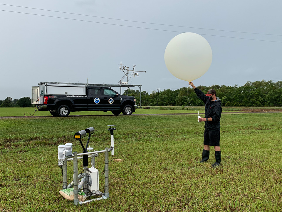 Researcher wearing medical mask holding weather balloon in a field